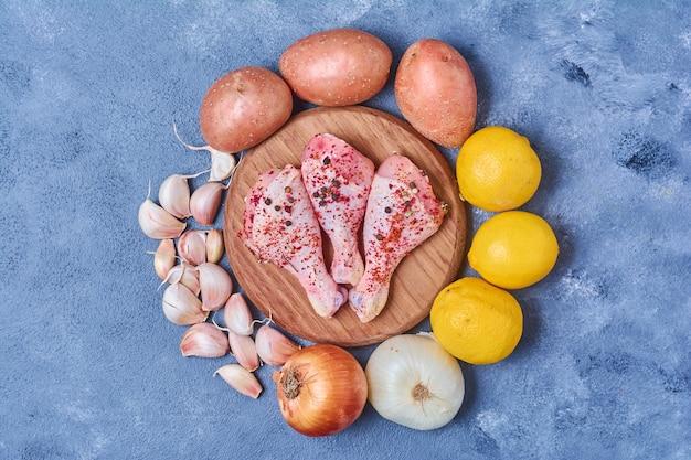 Куриные ножки с овощами на деревянной доске на синем
