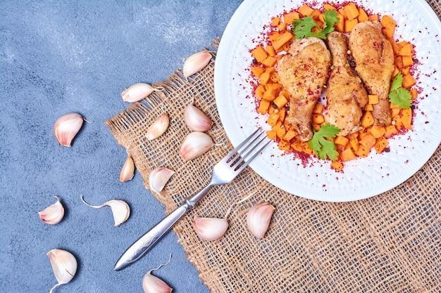 Cosce di pollo con verdure in un piatto bianco.