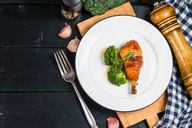 Chicken legs with vegetables on wooden table.