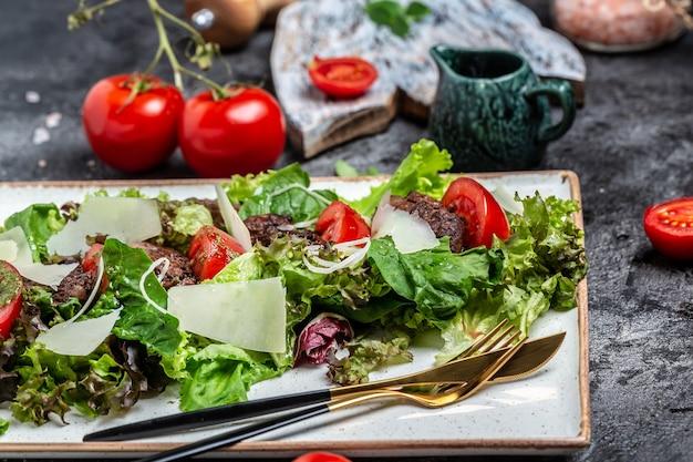 Куриная печень и листья салата, сыр пармезан и помидоры черри. вкусная концепция сбалансированного питания