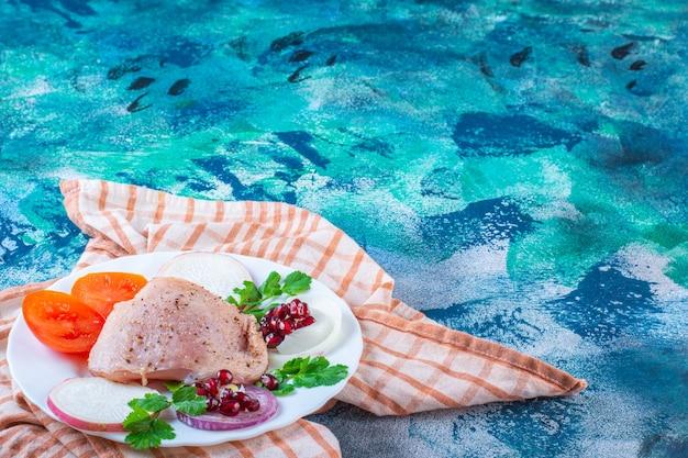 Куриная печень, листья салата и куриная голень на тарелке на кухонном полотенце
