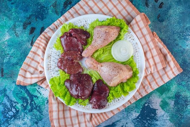 Fegato di pollo, foglie di lattuga e coscia di pollo su un piatto sul canovaccio