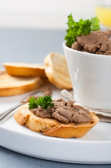 Chicken liver pate on bread and in bawl