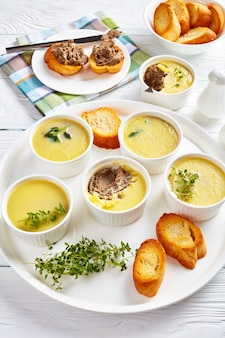 Chicken liver pate with herbs and butter in ramekins on a platter with toasted slices of baguette and pate liver sandwiches on a plate
