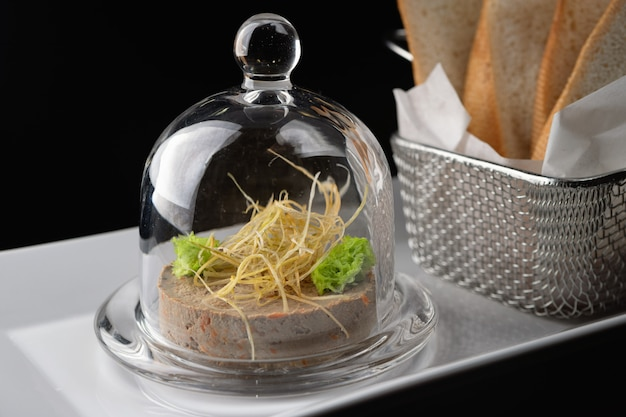 Chicken liver pate with leek fries, under a glass cover.