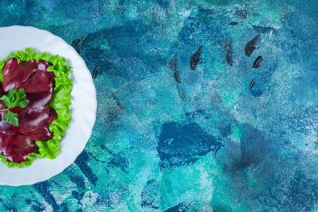 Куриная печень на листе салата на тарелке