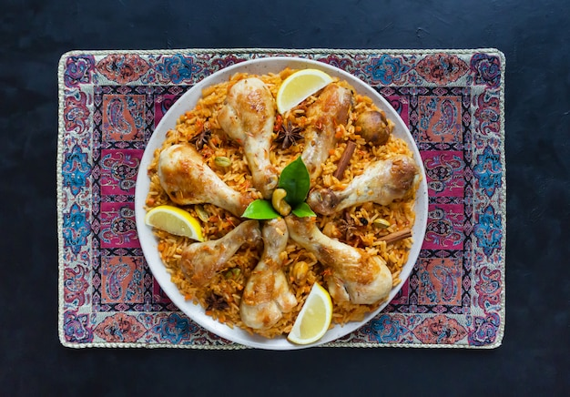 Chicken mandi with dates on a black table. arabic cuisine. top view.