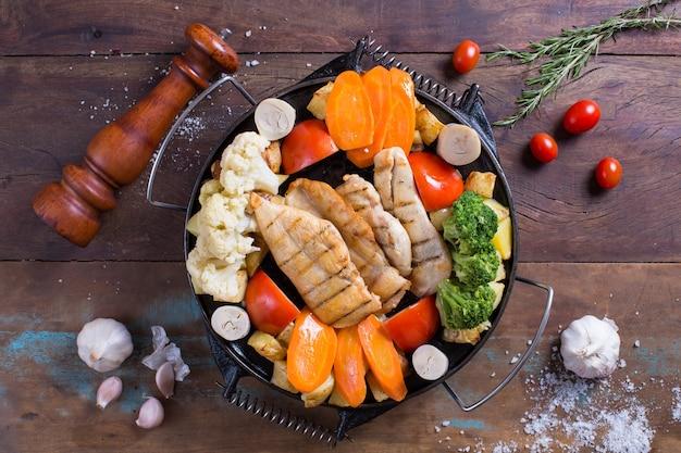 木製のテーブルに鶏肉と野菜