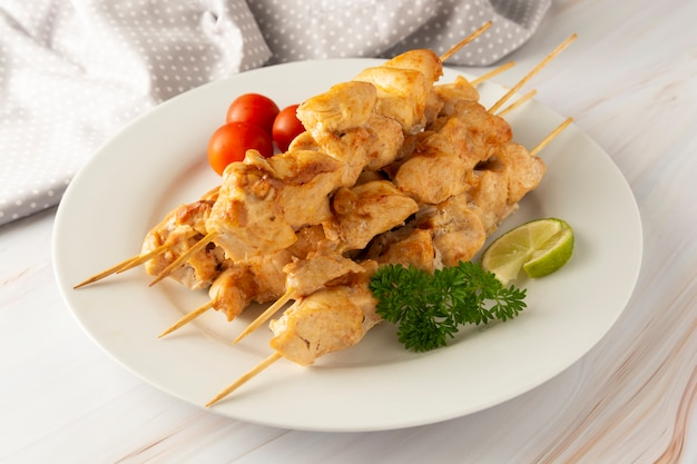 Chicken meat on bamboo skewers kebab in white plate, marble bright background. diet low fat food.