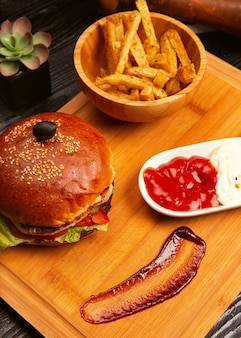 Chicken meat burger with tomato slices and lettuce served with french fries, ketchup and mayonnaise on wooden board