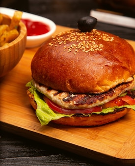 Chicken meat burger with tomato slices and lettuce served with french fries, ketchup and mayonnaise on wooden board.