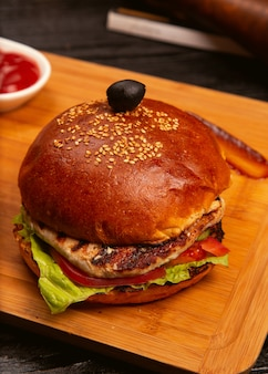 Chicken meat burger with tomato slices and lettuce served with , ketchup and mayonnaise on wooden board