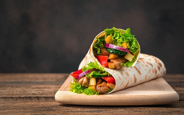 Chicken meat, french fries, vegetables and salad are wrapped in pita bread on a brown wall. traditional shawarma. side view, copy space.