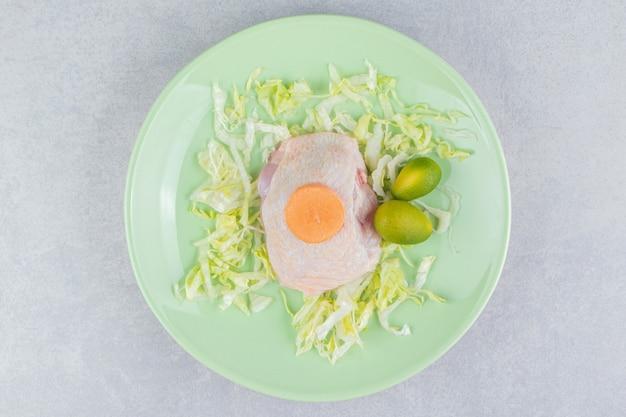 Carne di pollo sui verdi con kumquat e carota nel piatto, sulla superficie bianca