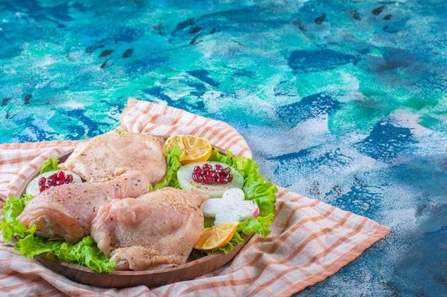 Куриное мясо, лимон, гранатовые орехи на деревянной тарелке на кухонном полотенце