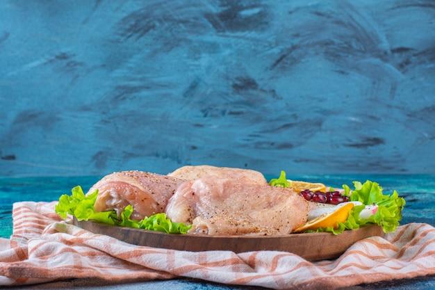 Carne di pollo, limone, arilli di melograno su un piatto di legno sul canovaccio