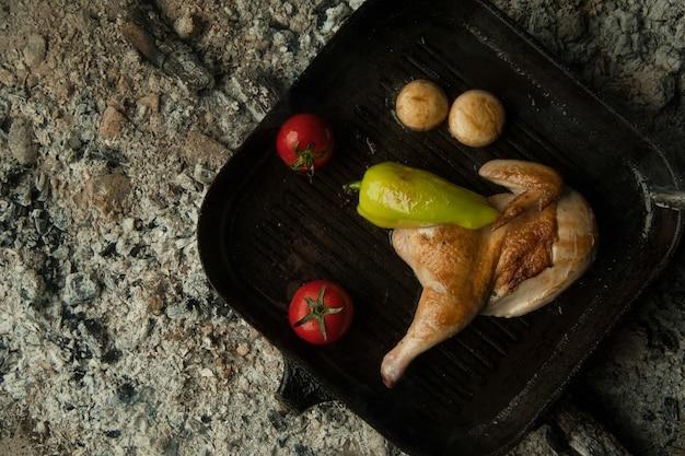 Куриное мясо с помидорами на противне лежать на углях блюдо готовится и коптится на углях.