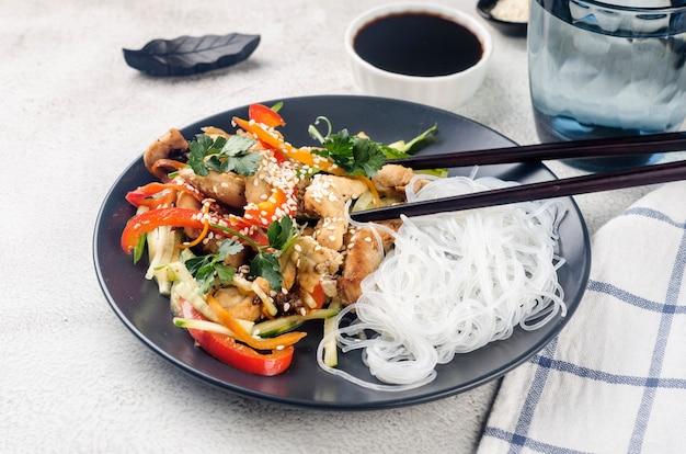 Куриное мясо с овощами вок и китайской рисовой лапшой, соусами и кунжутом в черной миске с китайскими палочками на светло-сером фоне. традиционная азиатская кухня.