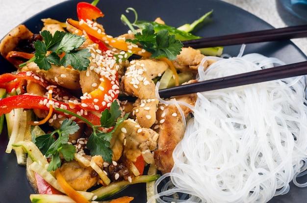 Куриное мясо с овощами вок и китайской рисовой лапшой, соусами и кунжутом в черной миске с