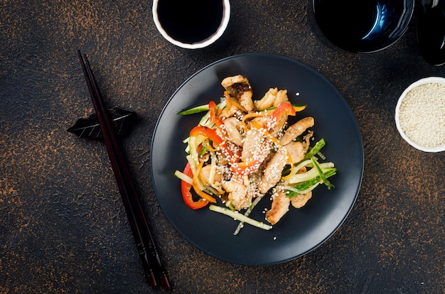 Куриное мясо с овощами вок, соевый соус и кунжут в черной тарелке с китайскими палочками для еды на темном фоне. традиционная азиатская кухня. копировать пространство