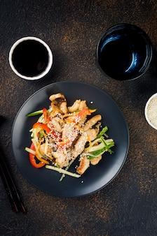 Куриное мясо с овощами вок, соевым соусом и кунжутом в черной тарелке с китайскими палочками для еды