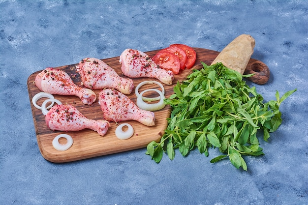 Chicken meat with vegetables on a wooden board on blue