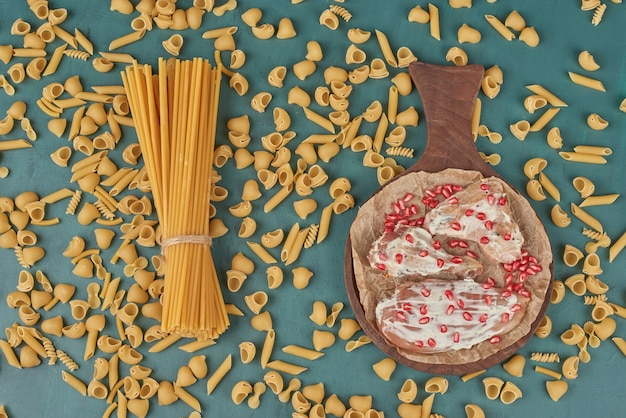 Carne di pollo su una tavola di legno con pasta e semi di melograno, vista dall'alto.