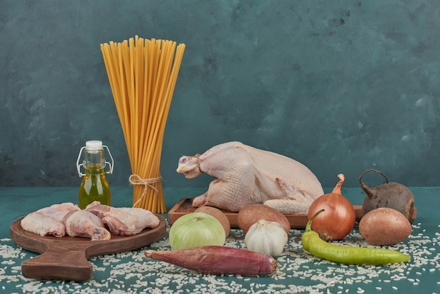 Chicken meat on a wooden board with pasta and vegetables around.