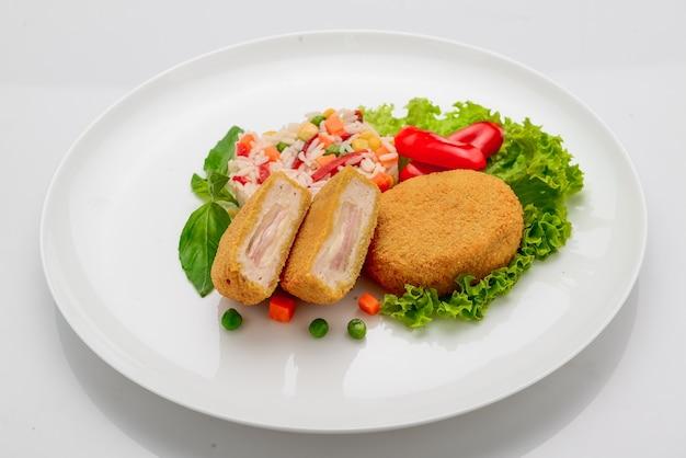 햄과 리조또를 곁들인 반죽에 닭고기 미트볼. 흰 바탕.