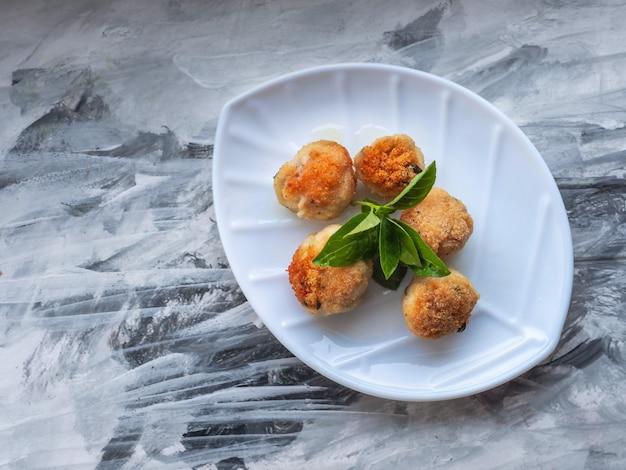 Куриные тефтели с веточкой базилика на белой фигурной тарелке в виде листика