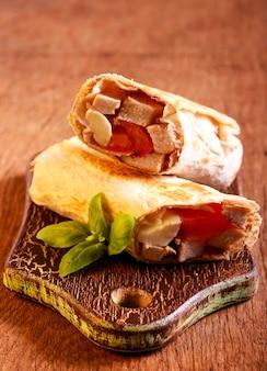 Chicken, mozzarella and tomato grill wrap on board