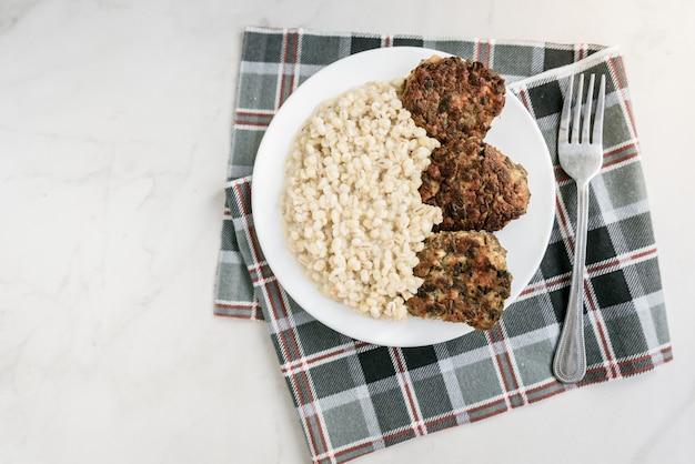 Котлеты из куриных грибов и перловой каши на белой тарелке