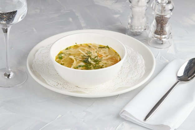 Chicken noodle soup, restaurant serving, light background