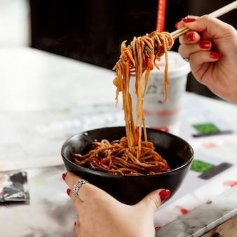 Chicken noodles in a black bowl
