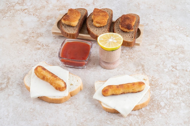 Chicken nugget and sausage sandwiches with lemon and ketchup.