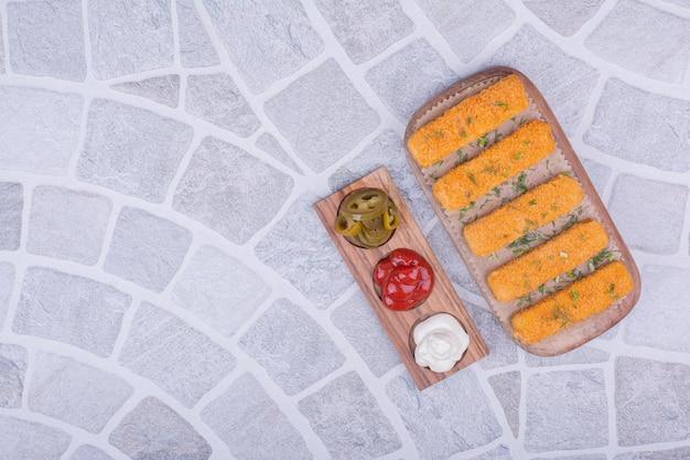 Bastoncini di pepita di pollo su un piatto di legno con salse.