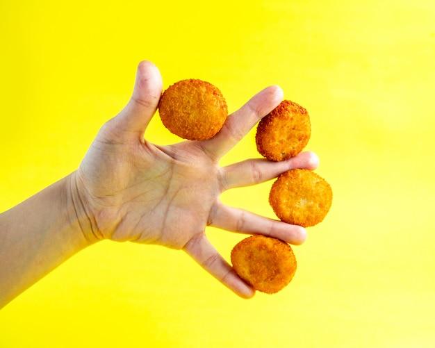 Куриные наггетсы между пальцами человека, вид сбоку