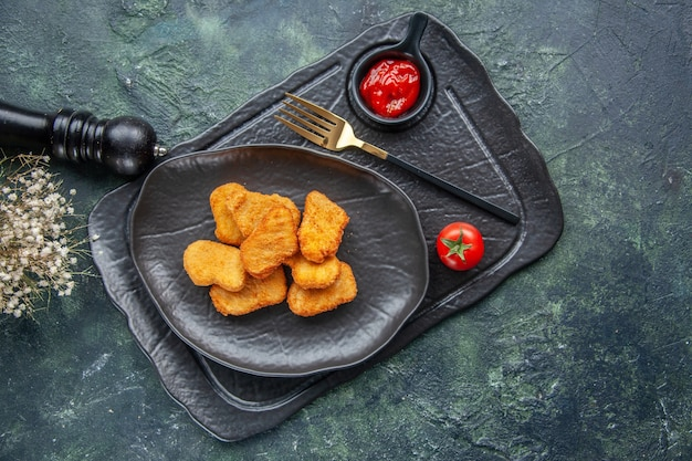 Chicken nuggets on a black plate and elegant fork ketchup on dark color tray white flower