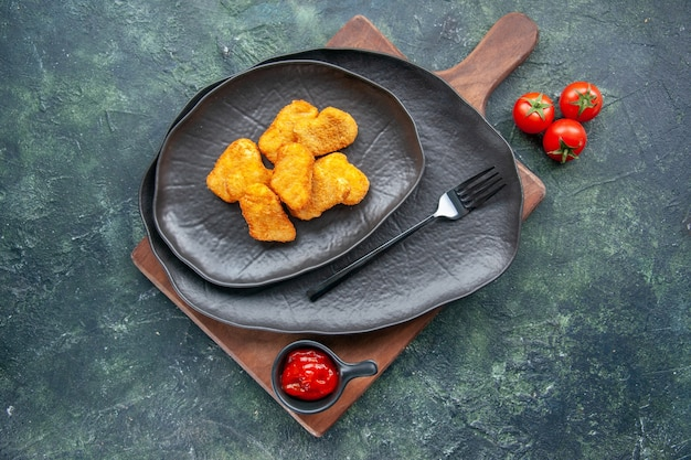 Chicken nuggets on a black plate and fork on wooden board tomatoes ketchup on dark surface