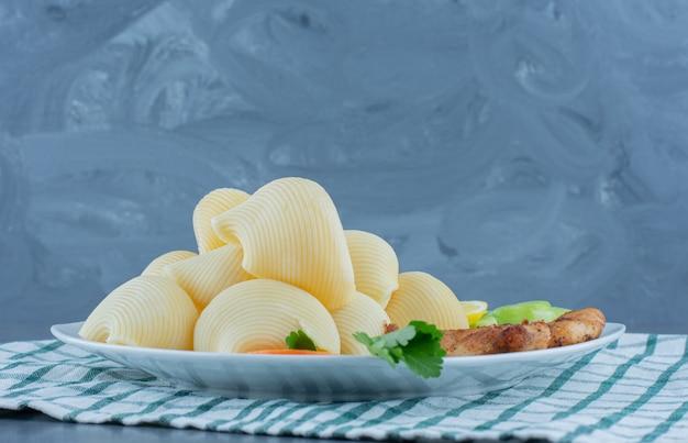 Pepite di pollo e pasta bollita sul piatto bianco.