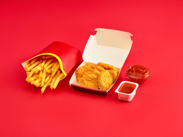 Chicken nuggets and french fries on red