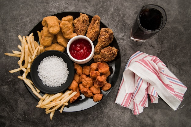 Chicken nuggets; fried chicken drumstick; crispy chicken popcorn; french fries with softdrink and napkin on concrete background