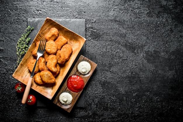 黒い木製のテーブルの上にフォーク、タイム、さまざまなソースが入ったプレートのチキンナゲット
