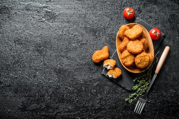 素朴なテーブルの上にフォーク、タイム、トマトを入れたボウルのチキンナゲット。