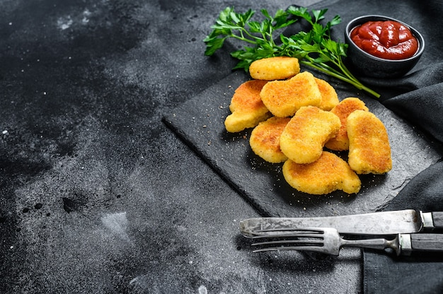 Chicken nuggets and ketchup sauce on the blackboard. dark background. top view. copy space.