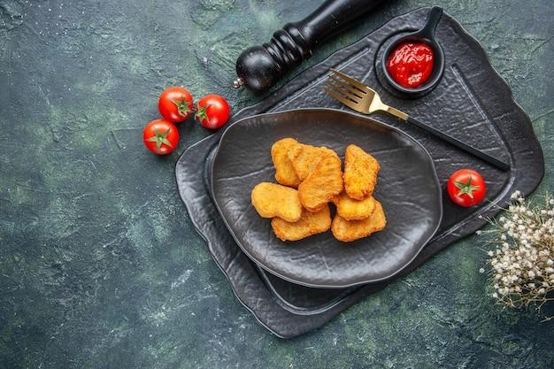 黒い皿にチキンナゲット、ダークトレイにエレガントなフォーク ケチャップ、白い花トマト
