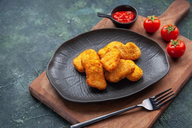 黒い皿にチキンナゲットと木の板にフォーク トマト ケチャップを暗い表面に、空きスペースをクローズ アップ ショット