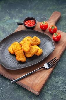 黒い皿にチキンナゲットと木の板にフォーク トマト ケチャップ、暗い表面に空きスペースをクローズ アップ ビュー