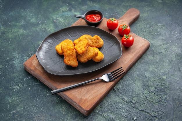 黒い皿にチキンナゲットと木の板にフォーク トマトケチャップ、空きスペースのある暗い表面に