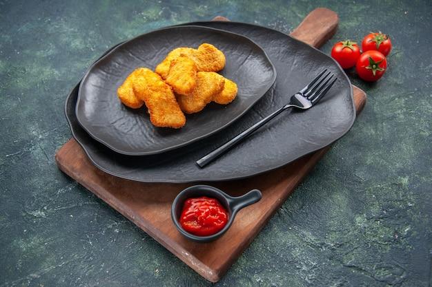 黒い皿にチキンナゲット、暗い面に木の板にフォーク トマト ケチャップ